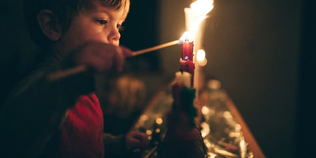 LÊER -- A boy lights a row of candles for the Advent season, a time of remembrance and reflection on the coming birth of Jesus Christ and the Christmas season.