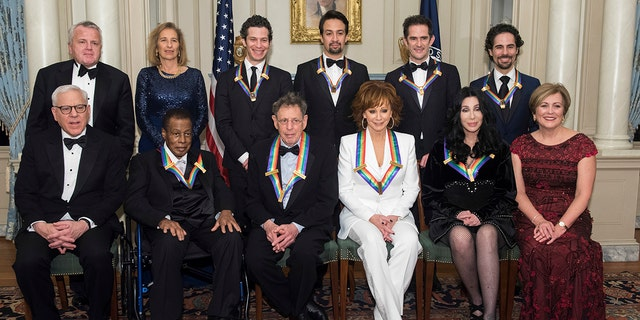 """Front row from left, David Rubenstein, 2018 Kennedy Center Honorees Wayne Shorter, Philip Glass, Reba McEntire, Cher, Kennedy Center President Deborah Rutter; back row from left, Deputy Secretary of State John Sullivan, Grace Rodriguez, and the 2018 Kennedy Center Honorees, the co-creators of """"Hamilton,"""" Thomas Kail, Lin-Manuel Miranda, Andy Blankenbuehler, and Alex Lacamoire pose for the group photo at the State Department following the Kennedy Center Honors State Department Dinner on Saturday, Dec. 1, 2018, in Washington."""