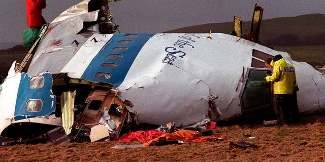 In this Dec 22, 1988 file photo, police and investigators look at what remains of the flight deck of Pan Am 103 in a field in Lockerbie, Scotland.