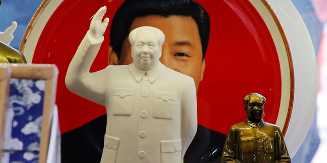 Sculptures of the late Chinese Chairman Mao Zedong are placed in front of a souvenir plate featuring a portrait of Chinese President Xi Jinping at a shop next to Tiananmen Square in Beijing, China, March 1, 2018. REUTERS/Jason Lee - RC19877D4F20