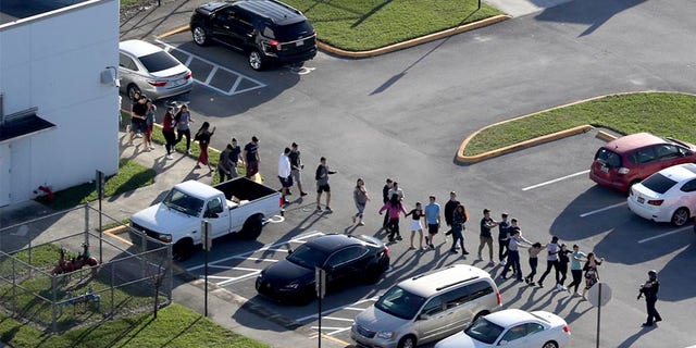 Students are evacuated by police from Marjory Stoneman Douglas High School in Parkland, Fla., during the shooting that took place there in February.