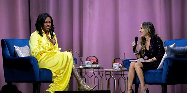 """Former first lady Michelle Obama, left, is interviewed by Sarah Jessica Parker during an appearance for her book, """"Becoming: An Intimate Conversation with Michelle Obama"""" at Barclays Center on Wednesday, Dec. 19, 2018, in New York. (AP Photo/Frank Franklin II)"""