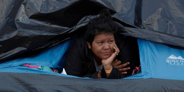 A woman rests inside a tent on the street near a sports complex shelter as authorities tried to persuade migrants to move to a new, more distant shelter, in Tijuana, Mexico, Saturday, Dec. 1, 2018. (AP Photo/Rebecca Blackwell)