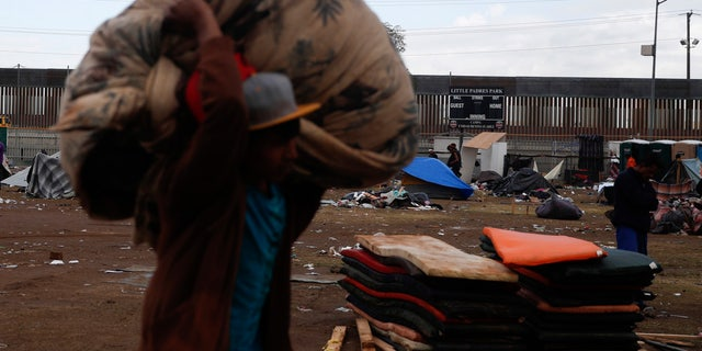 A migrant helps bundle and clear trash as most Central Americans leave a sports complex shelter that authorities were trying to close, in Tijuana, Mexico, Saturday, Dec. 1, 2018. (AP Photo/Rebecca Blackwell)
