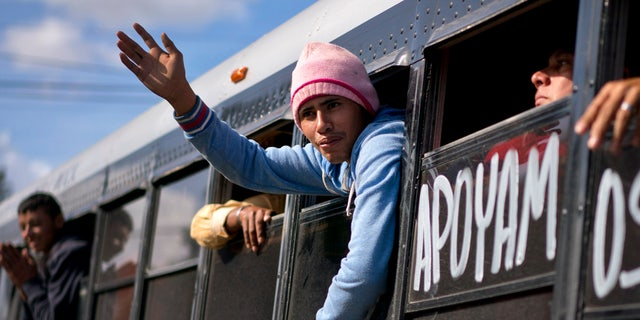 A migrant greets people while being transferred via a bus to a new shelter in Tijuana, Mexico, Saturday, Dec. 1, 2018. (AP Photo/Ramon Espinosa)