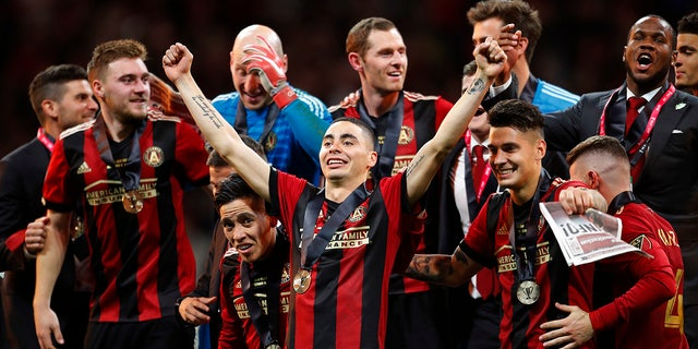 Atlanta United midfielder Miguel Almiron (10) celebrates with his teammates as they take the stage for the trophy presentation after the MLS Cup championship soccer game against the Portland Timbers, Saturday, Dec. 8, 2018, in Atlanta. Atlanta United won 2-0. (AP Photo/Todd Kirkland)