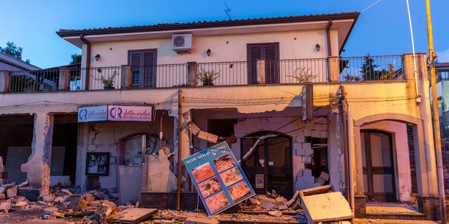 Debris sits on the street in front of a heavily damaged house in Fleri, Sicily Italy, Wednesday, Dec. 26, 2018.