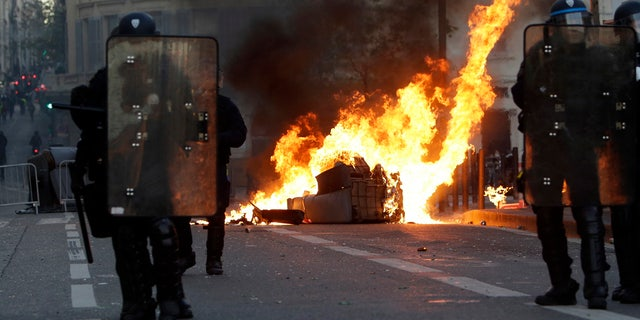 Riot police officers stand in front a burning trash bin during clashes, Saturday, Dec. 8, 2018 in Marseille, southern France.