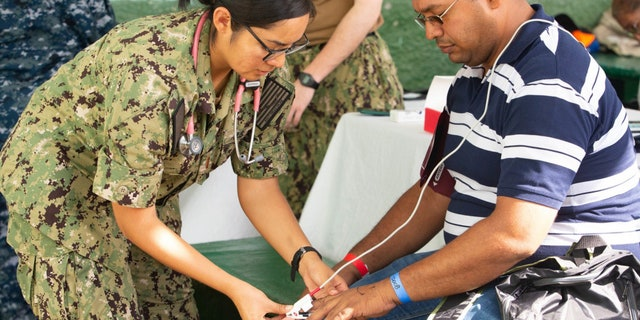 Ensign Kimberly Hill, from Phoenix, Ariz., takes the vitals of a patient during a medical screening at one of two medical sites.