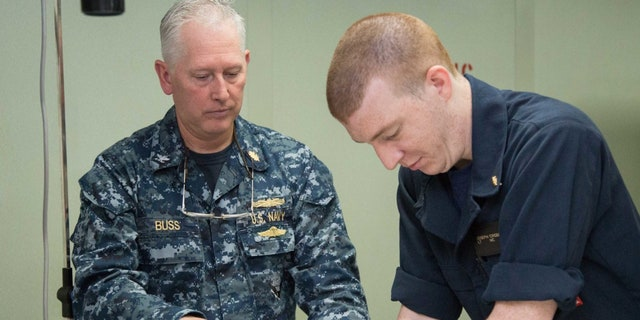 U.S. Navy Capt. Kevin Buss (left), director, nursing services, and Lt. Joseph Crossman, a midwife from Chesapeake, Va., participate in an advanced cardiac life support certification course in the intensive care unit aboard the hospital ship USNS Comfort (T-AH 20).