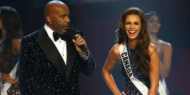 Miss Canada Marta Stepien gestures as host Steve Harvey greets her during the final of 67th Miss Universe competition in Bangkok, Thailand, Monday, Dec. 17, 2018.(Associated Press)
