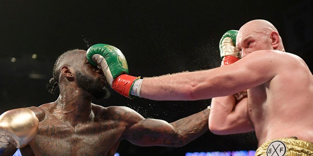 Deontay Wilder, left, and Tyson Fury, of England, trade punches during a WBC heavyweight championship boxing match Saturday, Dec. 1, 2018, in Los Angeles. (AP Photo/Mark J. Terrill)