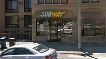 Subway employee photographed with bare feet on counter near food storage