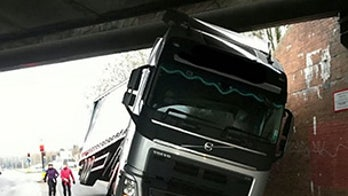 Semi truck gets very stuck under bridge
