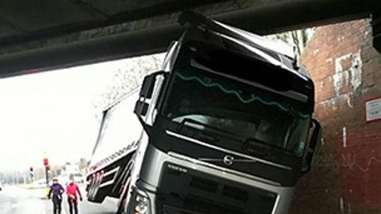 Semi truck gets very stuck under bridge