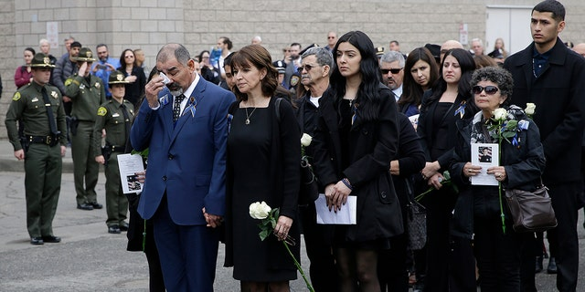 Merced Corona, left, and Lupe Corona, the parents of Davis Police Officer Natalie Corona, watch as her coffin is taken to a hearse after funeral services for Davis Police Officer Natalie Corona at the University of California, Davis, Friday, Jan. 18, 2019, in Davis, Calif. (Associated Press)