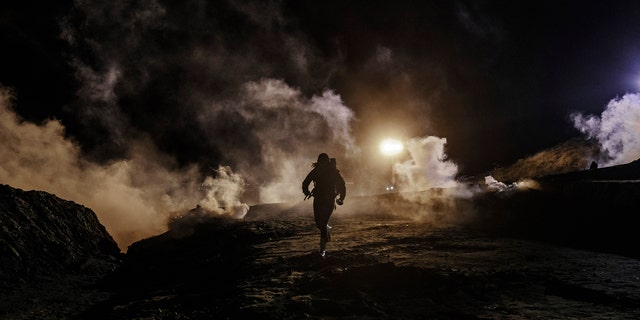Migrants running as U.S. Border Protection officers threw tear gas to the Mexican side of the border fence on Jan. 1, 2019. (AP Photo/Daniel Ochoa de Olza)
