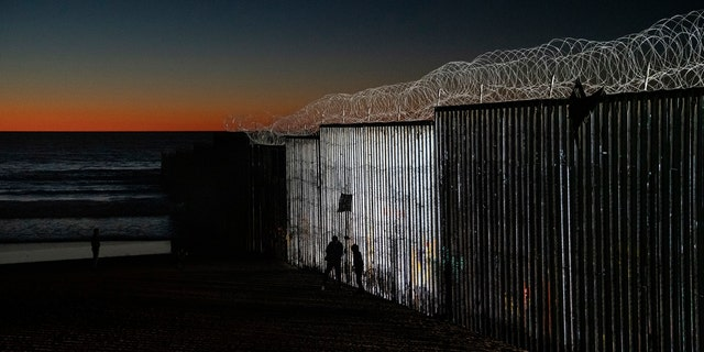 The sun sets while people get close to the border fence between the U.S. side of San Diego, Calif., and Tijuana, in Mexico, Wednesday, Jan. 2, 2019.