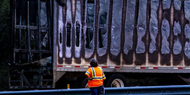 A worker looks at a charred semi-truck after a wreck with multiple fatalities on Interstate 75, south of Alachua, near Gainesville, Fa., Thursday, Jan. 3, 2019. Two big rigs and two passenger vehicles collided and spilled diesel fuel across the Florida highway Thursday, sparking a massive fire that killed several people, authorities said.