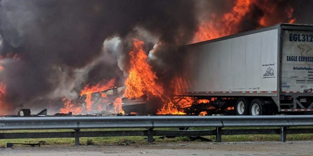 Flames engulf vehicles after a fiery crash along Interstate 75, Thursday, Jan. 3, 2019, about a mile south of Alachua, near Gainesville, Fla. Highway officials say at least six people have died after a crash and diesel fuel spill sparked a massive fire along the Florida interstate.