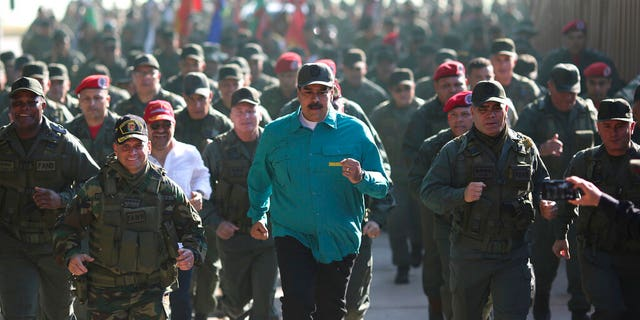 In this photo released to the media by Miraflores presidential palace press office, Venezuelan President Nicolas Maduro, center, jogs alongside his Defense Minister Vladimir Padrino Lopez, right, and soldiers as he visits Ft. Paramacay in Carabobo state, Venezuela, Sunday, Jan. 27.
