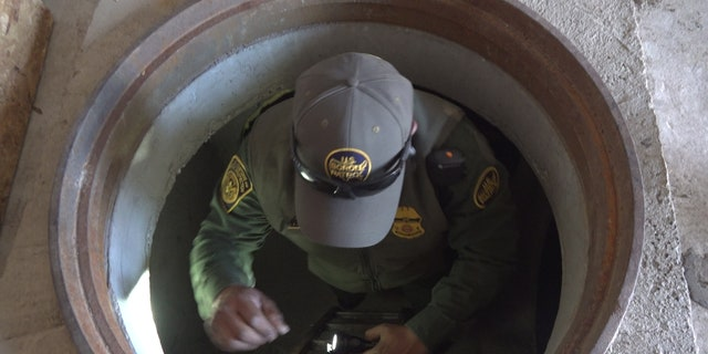 A Border Patrol agent demonstrates climbing into and out of the mock tunnels used for training at the Border Patrol Tucson Sector Nogales Station.