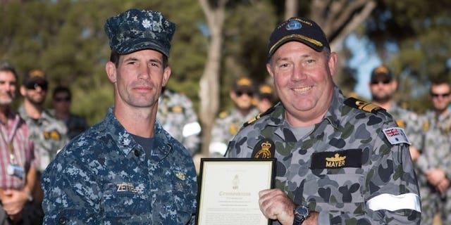 Commander Australian Fleet Rear Admiral Stuart Mayer, CSC and Bar, RAN, presents Commander Travis Zettel USN (left), with a Commander Australian Fleet Silver Commendation for his achievements as Staff Officer Grade One, Operations Support at HMAS Stirling, Western Australia.