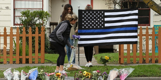 Sydney Carlier, foreground, accompanied by roommates, Jenna Brouwer, center and Camille Foder, behind flag, places flowers on a memorial for slain Davis Police Officer Natalie Corona, on Friday in Davis, Calif.