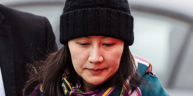 In this Dec. 12, 2018, file photo, Huawei chief financial officer Meng Wanzhou arrives at a parole office with a security guard in Vancouver, British Columbia. China on Tuesday, Jan. 22, 2019, demanded the U.S. drop a request that Canada extradite the top executive of the tech giant Huawei.
