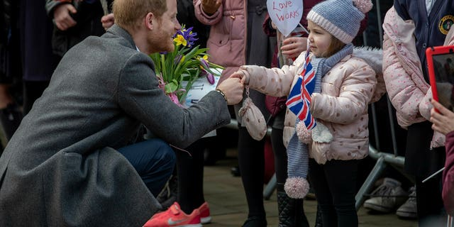 Britain's Prince Harry, with Meghan, Duchess of Sussex, greets the crowds of people during a visit to Birkenhead, northwest England, Monday Jan. 14, 2019. (Charlotte Graham/Pool via AP)