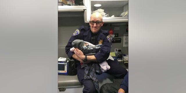 California Highway Patrol Officer Jeffrey Lloyd holds a baby he helped deliver along Highway 99 on Monday. (CHP South Sacramento)