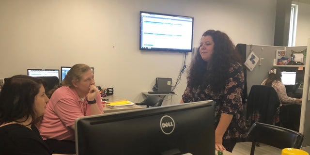ViaLink coordinators talk as a crisis counselor offers help over the phone.