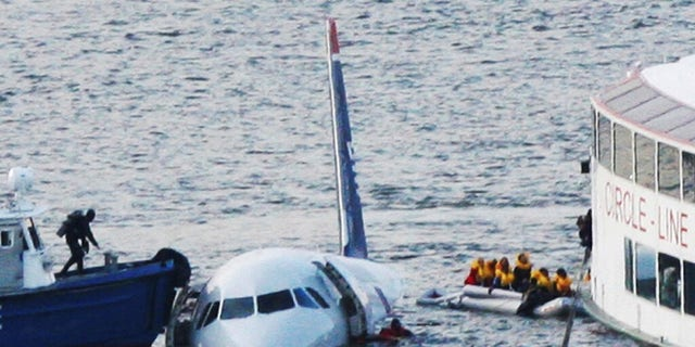 """This Jan. 15, 2009 photo shows a diver, left, aboard an NYPD vessel prepares to rescue passengers that escaped from the Airbus 320 US Airways aircraft made an emergency landing in the Hudson River in New York in what came to be known as the """"Miracle on the Hudson"""" because everyone survived."""
