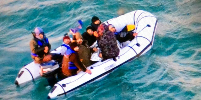 This image provided by the Marine Nationale (French Navy) shows migrants aboard a rubber boat after being intercepted by French authorities, off the port of Calais, northern France, Tuesday, Dec. 25, 2018. (Marine Nationale via AP)
