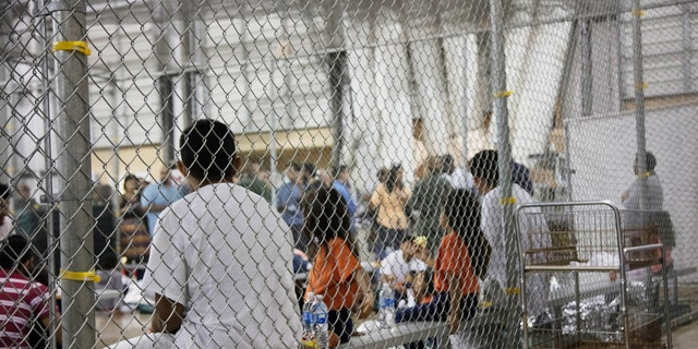 In this June 2018 photo provided by U.S. Customs and Border Protection, people who've been taken into custody related to cases of illegal entry into the United States, sit in one of the cages at a facility in McAllen, Texas.