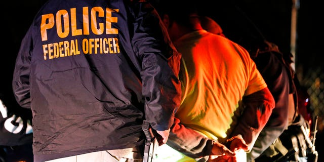 In this Oct. 22, 2018, photo U.S. Immigration and Customs Enforcement agents surround and detain a person during a raid in Richmond, Va. ICE's enforcement and removal operations