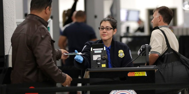 A Transportation Security Administration officer works at a checkpoint at Miami International Airport, Sunday, Jan. 6, 2019, in Miami. The TSA acknowledged an increase in the number of its employees calling off work during the partial government shutdown. (AP Photo/Lynne Sladky)