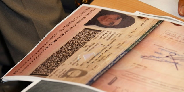 A passport copy of Rahaf Mohammed Alqunun sits on the desk as Chief of Immigration Police Maj. Gen. Surachate Hakparn talks to media about her status during a press conference at the Suvarnabhumi Airport in Bangkok. (AP Photo/Sakchai Lalit)
