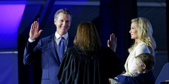 California Governor Gavin Newsom taking the oath of office from state Supreme Court Chief Justice Tani Gorre Cantil-Sakauye during his inauguration Monday in Sacramento, Calif. Looking on: Newsom's wife, Jennifer Siebel Newsom and their sons, Dutch, second from right, and Hunter, right. (AP Photo/Rich Pedroncelli)