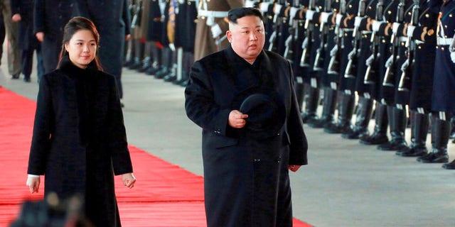 North Korean leader Kim Jong Un walks with his wife Ri Sol Ju at Pyongyang Station in Pyongyang, North Korea, before leaving for China.