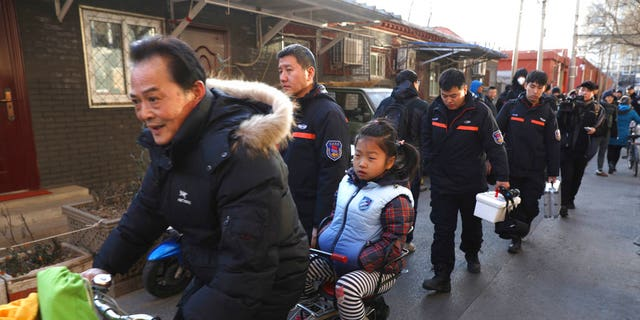 A man rides with a student past crime scene investigators as they leave the Beijing No. 1 Affiliated Elementary School of Xuanwu Normal School in Beijing, China, Tuesday, Jan. 8, 2019.