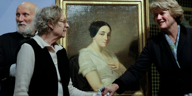 Government Commissioner for Culture and the Media Monika Gruetters, right, overhands the painting 'Portrait of a Seated Young Woman' by Thomas Couture to Franz Rainer Wolfgang Joachim Kleinertz, left, and Maria de las Mercedes Estrada, second from left, heirs of Jewish French politician Georges Mandel, during a restitution ceremony in Berlin. (AP Photo/Markus Schreiber)