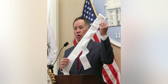 Assemblyman Phil Ting, D-San Francisco, displays a long paper receipt as he discusses his bill to require businesses to offer electronic receipts, Tuesday, Jan. 8, 2019, in Sacramento, Calif.