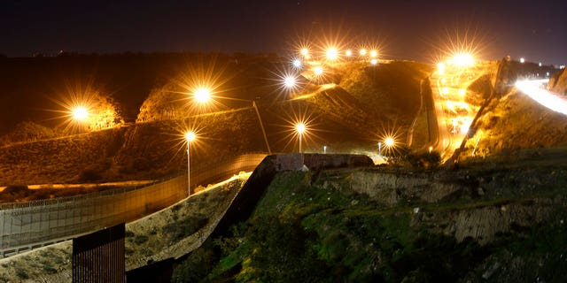 FILE - In this Monday, Jan. 7, 2019, file photo, floodlights from the U.S, illuminate multiple border walls, seen from Tijuana, Mexico. (AP Photo/Gregory Bull, File)