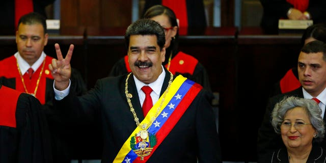Nicolas Maduro makes a victory sign during his swearing-in ceremony at the Supreme Court in Caracas, Venezuela, Thursday, Jan. 10, 2019.