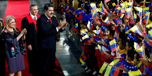 Venezuela's President Nicolas Maduro and first lady Cilia Flores stop to greet flag-waving children upon arrival to the Supreme Court for Maduro's inauguration ceremony in Caracas, Venezuela, Thursday, Jan. 10, 2019.