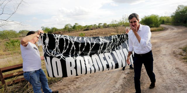 """FILE - In this Saturday, Jan. 6, 2018, file photo, Texas Democratic Congressman Beto O'Rourke, right, passes a """"No Border Wall"""" sign during a visit to the National Butterfly Center in Mission, Texas, a possible location for a border wall. President Donald Trump is not giving up on his demands for $5.7 billion to build a wall along the U.S.-Mexico border, saying a physical barrier is central to any strategy for addressing the security and humanitarian crisis at the southern border. Democrats argue that funding the construction of a steel barrier along roughly 234 miles will not solve the problems. (AP Photo/Eric Gay, File)"""