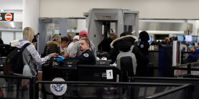 A Transportation Security Administration officer works at the entrance to Concourse G at Miami International Airport, Friday, Jan. 11, 2019, in Miami. The airport is closing Terminal G this weekend as the federal government shutdown stretches toward a fourth week because security screeners have been calling in sick at twice the airport's normal rate. (AP Photo/Lynne Sladky)