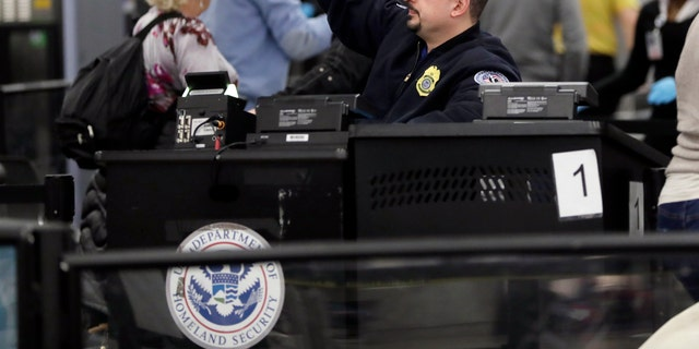 A Transportation Security Administration officer works at the entrance to Concourse G at Miami International Airport, Friday, Jan. 11, 2019, in Miami. The airport is closing Terminal G this weekend as the federal government shutdown stretches toward a fourth week because security screeners have been calling in sick at twice the airport's normal rate.