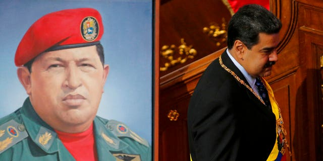 Venezuela's President Nicolas Maduro walks past a painting of his predecessor, late President Hugo Chavez, inside the chambers of the Constitutional Assembly where he will give his annual address to the nation in Caracas, Venezuela, Monday, Jan. 14, 2019.